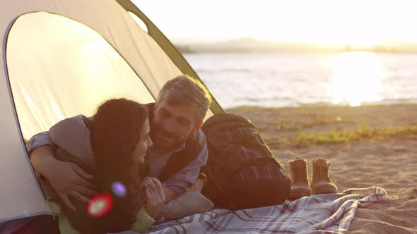 Thumbnail for Romantic Couple Embracing and Talking in Tent on Beach at Sunset