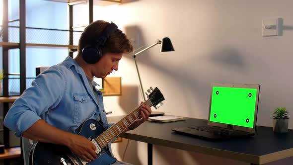 Thumbnail for Man in Headphones Playing Bass Guitar at Home