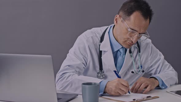 Thumbnail for Caucasian Physician Sits at a Desk and Writes Research Results on Paper