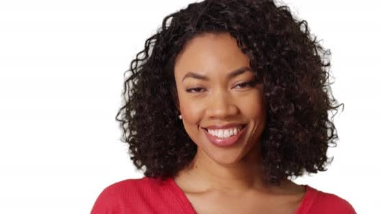Closeup of cute black female with curly hair and beautiful smile in studio