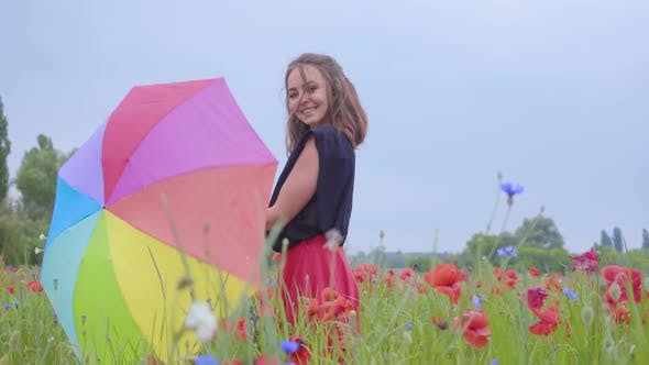 Thumbnail for Cute Young Girl Spinning Colorful Umbrella Dancing in a Poppy Field Smiling Happily Looking