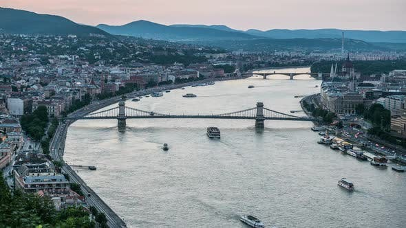 Thumbnail for Pleasure Boats Sailing Down Danube River Under Bridges, Day-To-Night Time-Lapse