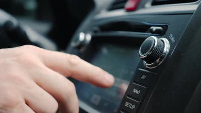 Male Hand Tunes the Radio in the Car