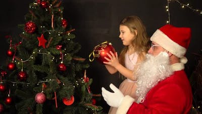 Santa Claus and a little girl decorate a Christmas tree. Santa holds the girl in his arms