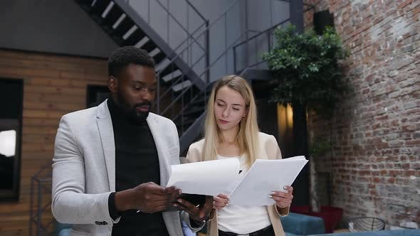 Thumbnail for Businessman Revisioning Different Documents with His Blond Stunning Female Colleague