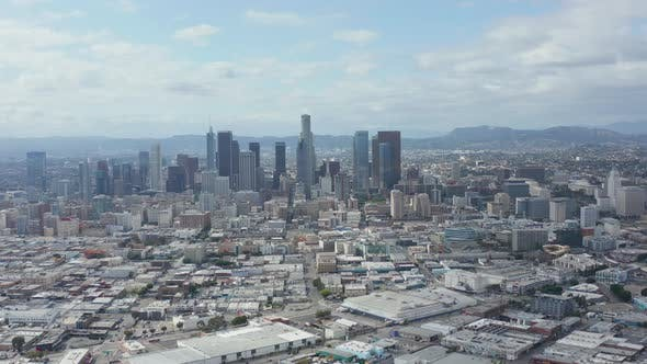 Thumbnail for AERIAL: Slow Side Shot of Downtown Los Angeles Skyline with Warehouse Art District in Foreground
