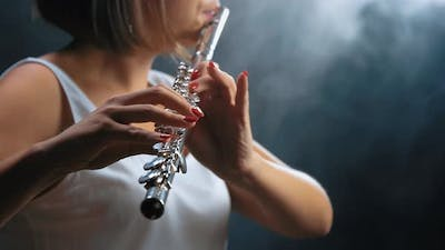 Professional Musician Female Playing on Flute. Smoky Studio
