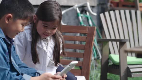 Thumbnail for Cute Kids Sitting on Bench and Playing on Tablet