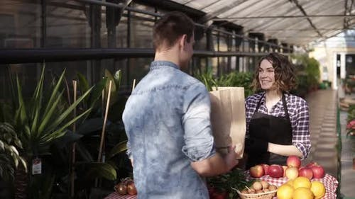 Cheerful Saleswoman in Black Apron Giving Fresh Vegetables in Paper Bag to Customer in Greenhouse