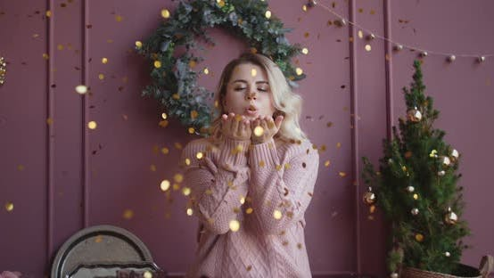 Beautiful Woman in Sweater Blows Shiny Confetti From Her Hands To the Camera in Slow Motion