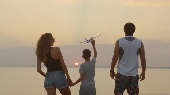 Cover Image for A Happy Family. The Boy with His Father and Mother with Toy Airplane at the Sunset