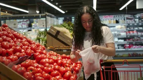 Young Woman in the Grocery Section of a Supermarket Picks Up a Bag and Puts Tomatoes in a Basket to