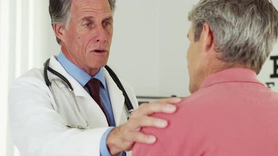 Happy senior doctor talking to elderly patient with hand on shoulder