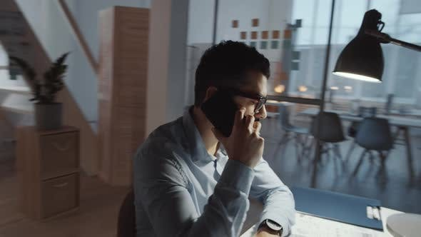Middle Eastern Male Office Worker Talking on Mobile Phone at Desk