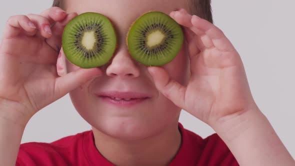 Thumbnail for Young boy holding kiwi fruit over eyes
