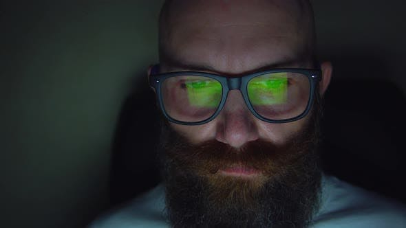 Thumbnail for Bearded Man in Eyeglasses Browsing Website at Late Night, Reflection at Glasses
