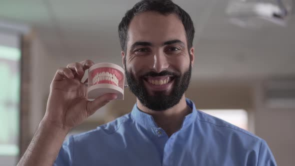 Thumbnail for Close-up Portrait of Young Middle Eastern Man Holding Teeth Cast and Smiling at Camera. Professional