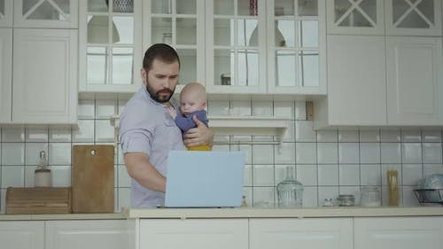 Father Working At Home Hodling Toddler