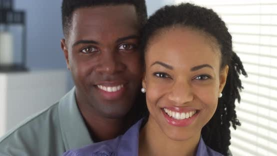 Thumbnail for Portrait of young black couple holding each other looking at camera