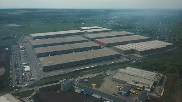Vehicles Near Modern Warehouse Buildings