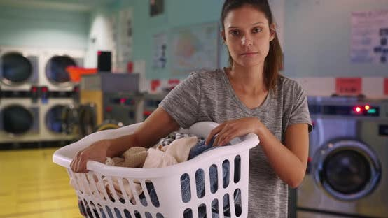 Thumbnail for Serious young woman in laundry room with machines holding basket of clothes