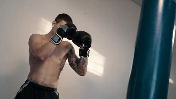 Free Fighter Has Punching Bag in Gym