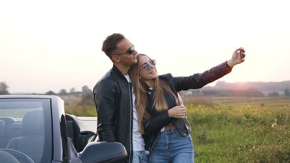 Thumbnail for Handsome Couple in Love Taking Selfie Standing Near the Car Cabriolet