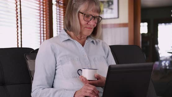 Thumbnail for Retired aged white woman drinking tea while using laptop computer in living room