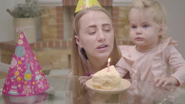 Thumbnail for Close-up of Young Caucasian Woman in Party Hat and Little Baby Girl Blowing Candle on the Piece