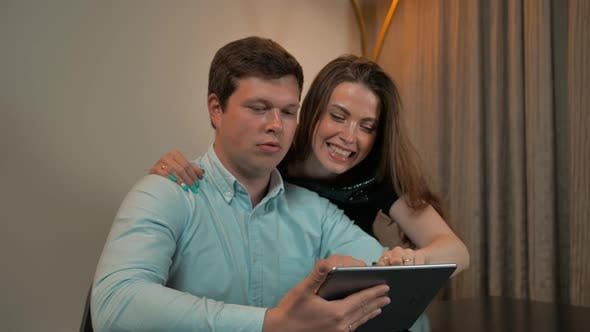 Attractive Couple Surf on Tablet in Home