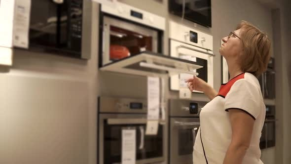 Retired Woman is Looking on Ovens in Retail Shop Opening Doors
