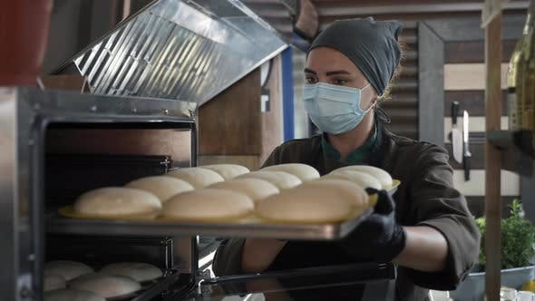 Small Business, Female Baker in Medical Mask Puts Bake with Slices of Dough for Baking