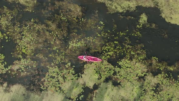 Thumbnail for Woman is floating in boat on vacation, drone top view. Female tourist is exploring river in kayak.