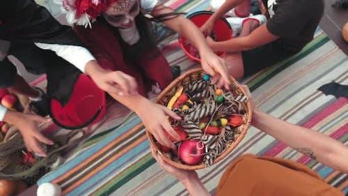 Draufsicht von Kindern in Kostümen Grabbing Süßigkeiten auf Halloween