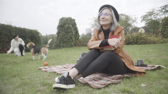 Thumbnail for Happy Elegant Senior Woman in Eyeglasses and Hat on Spring or Autumn Meadow with Book Smiling As