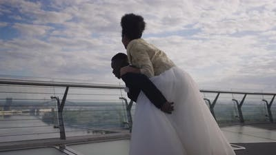 Laughing Groom Spinning Holding Bride on Back