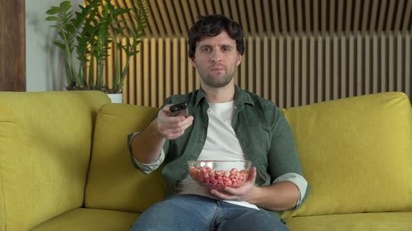 A Man in Front of the TV Watching a Sports Game or a Movie Sitting on a Yellow Sofa and Eating