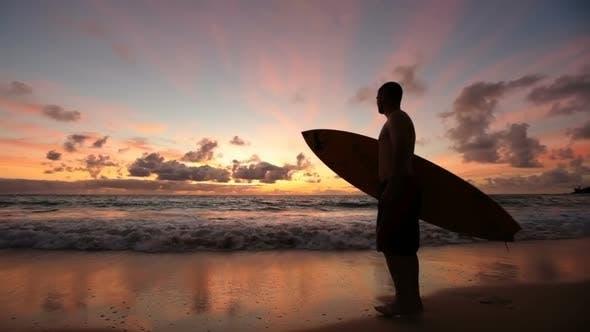 Thumbnail for Surfer walking along beach at sunrise, Hawaii