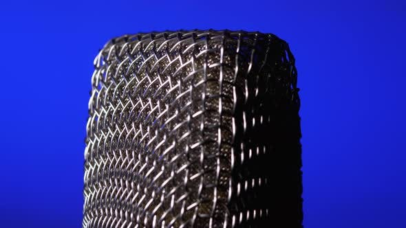 Cover Image for Studio Condenser Microphone Rotates on Blue Background.