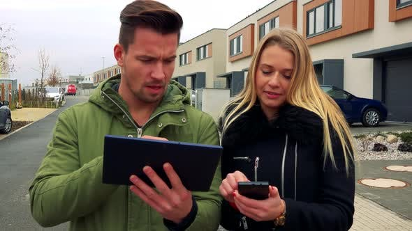 Thumbnail for A Man and a Woman Discuss Something About a Tablet and a Smartphone on a Road in a Neighborhood