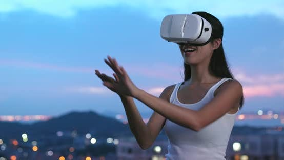 Thumbnail for Woman watching with virtual reality device in the sunset