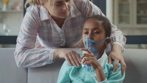 Thumbnail for Caring Mom Supports Unwell Child in Nebulizer Mask