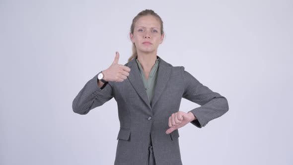 Thumbnail for Young Confused Blonde Businesswoman Choosing Between Thumbs Up and Thumbs Down