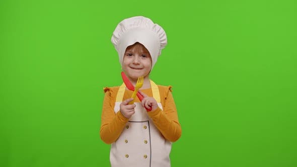 Child Girl Kid Dressed Cook Chef Baker in Apron and Hat with Plastic Fork and Knife Fooling Around