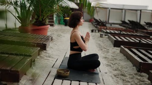 Woman Sits in Meditation on the Beach