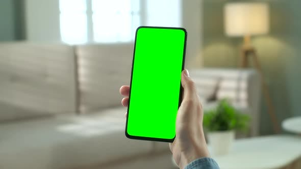 Thumbnail for Close Up View of Woman at Modern Room Sitting on a Chair Using Phone With Green Mock-up Screen