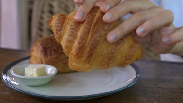 Close Up of Hands Breaking in Half Freshly Baked Crusty Flaky Buttery Croissant