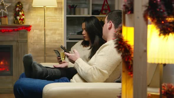 Romantic Couple Relaxing on Couch and Browsing on Their Phones
