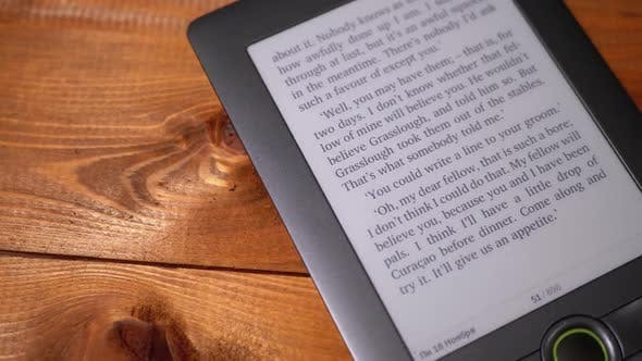 Thumbnail for The Electronic Book Lies on a Wooden Table. Screen of Electronic Ink Displays Text of the Book