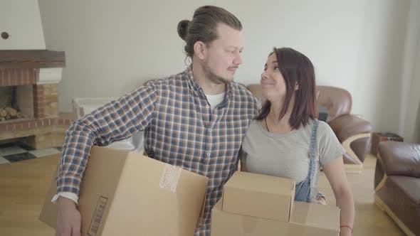 Cover Image for Portrait of Caucasian Couple Standing with Cardboard Boxes in Living Room and Smiling